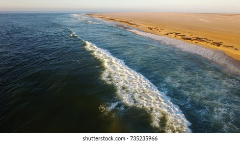 High quality aerial drone photo of desert sand peninsula, sea boat shipwreck remains, seals beach, Walvis Bay lagoon with view of distant sea ships at Namibia's Atlantic west coast, southern Africa