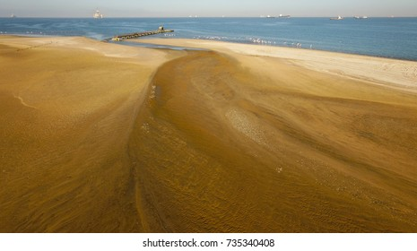 High quality aerial drone photo of desert sand peninsula, remains of lone rusty pier, birds beach, Walvis Bay lagoon with view of distant sea vessels at Namibia's Atlantic west coast, southern Africa