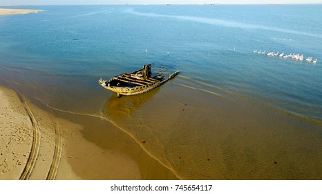 High quality aerial drone photo of desert sand peninsula, sea boat shipwreck remains, birds beach, Walvis Bay lagoon with view of distant sea vessels at Namibia's Atlantic west coast, southern Africa