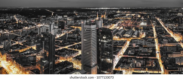 High quality black and white aerial panoramic view of Frankfurt, Germany at dusk. Yellow street traffic lights between the buildings.