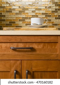 High quality cherry wood cabinets with bronze cabinet hardware, quartz countertops & glass tile mosaic backsplash in contemporary upscale home kitchen