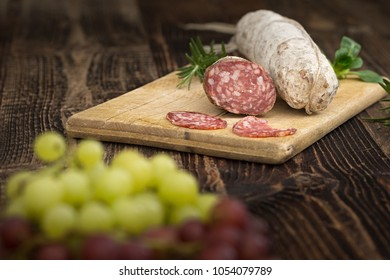 High - quality dried salami with rosemary, basil and grapes  on the wooden plate.