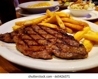 high quality photo of beef steak with fries with more food at background. Freshly made steak.