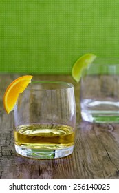 High quality tequila in a snifter with orange garnish and silver tequila in blurred background