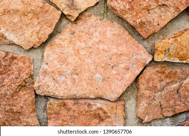 High quality texture of the natural red stone wall. Stone background. Stone in concrete. Red tan stone exterior finish.