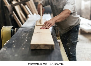 High quality wood concept. Cropped photo of mature cabinetmaker or handyman make furniture in garage or workroom using woodworking machine