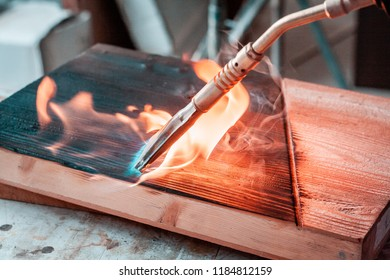 High quality wood planks and slabs, while being burnt with a brass, gas burner in woodshop in Italy. Details of the fire burst, and black wooden texture after the process.