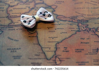 High resolution close up of the region of word India on a world vintage map with little retro barrette bow. Adventure stories background. Vintage style.