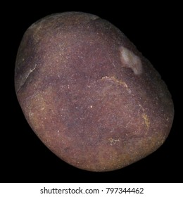 A high resolution macro close up of a reddish pebble or stone isolated against a black background