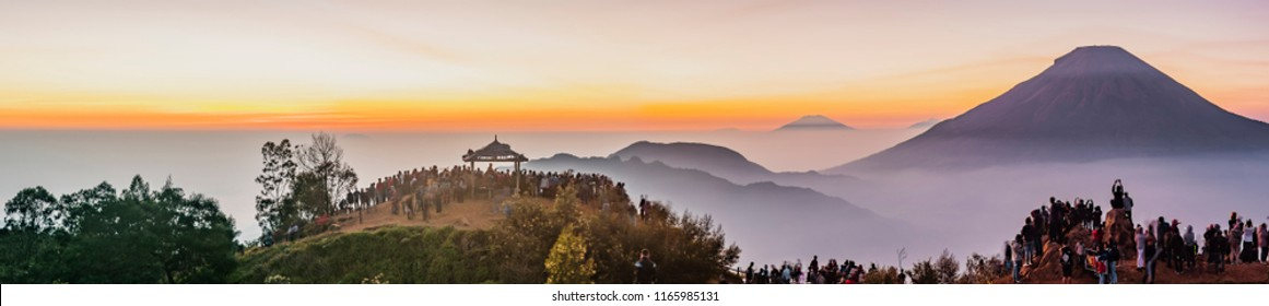 High resolution panorama shot of Sundoro volcano from Sikunir peak, Dieng Plateau in Indonesia with soft misty horizon layer background and foreground of people silhouette wait for sunrise on peak.