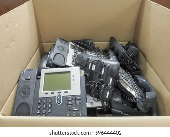 High resolution shot of old office telephone in the box waiting for recycle. Old technology office IP telephone in paper box refer to life cycle of old and new technology or business that close down