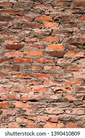High resolution texture of an old and damaged brick wall.Red brick wall with the darts made out of concrete. Old red brick that has been inaccurately restored and fixed. Rough brick wall
