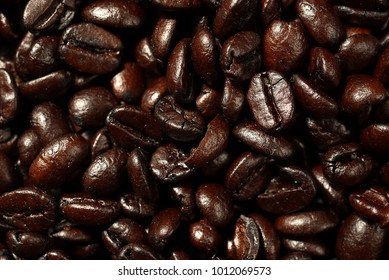 High resolution top view close up macro photo of look delicious dark roasted coffee beans, Flash light reflecting on the surface of the coffee beans make it look shinny beautiful and be nice for eat.