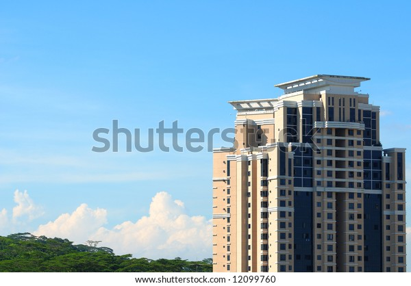 A high rise building against blue skies and vegetation