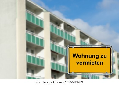 high rise building and town sign with the german words Apartment for rent