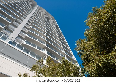 High rise condominium in Yokohama, Japan. Low angle view of the white building against blue sky. There are green trees in front of the structure.
