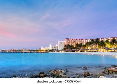 High Rise hotel area in Aruba at dusk. Palm trees in motion suggest the windy weather, a well known characteristic of this island, located on the southern fringes of the Caribbean