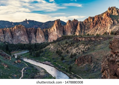 High rock cliff structures towering over a small river in Smith Rock State Park, near Bend, Oregon, USA, shot just before sunset.