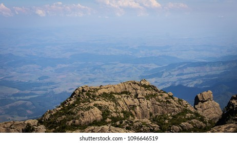 High rock mountain and horizon to background with blue sky and creeping green nature in Brazil.
