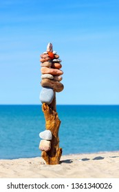 High rock zen pyramid of multi-colored stones on the background of the sea. Concept of balance, harmony and meditation