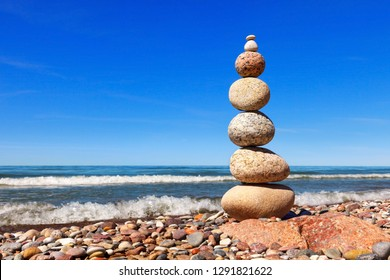 High Rock zen pyramid of white and pink pebbles on the beach. Concept of balance, harmony and meditation