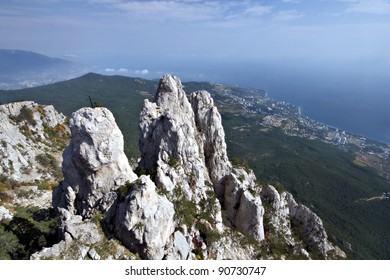 High rocks Ai-Petri of Crimean mountains with cross against a green forest, Black sea coast and blue sky with clouds. Ukraine.