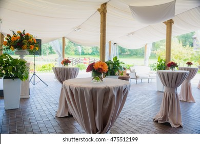 High round tables beautified with red bouquets stand under a white pavilion