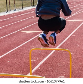 A high school athlete is jumping over a 2 foot high yellow hurdle on a track for speed and agility training during a workout on a cold and sunny day.