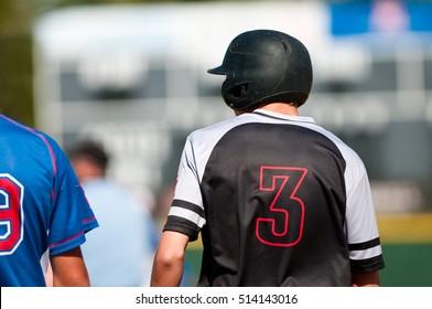 High school baseball boy standing on first base.