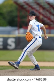 High school baseball pitcher delivering baseball to home plate