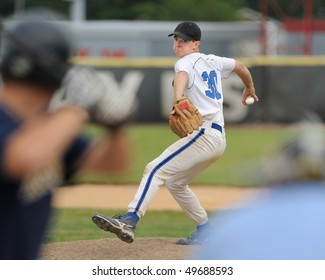 High school baseball pitcher delivering baseball to batter with umpire looking on