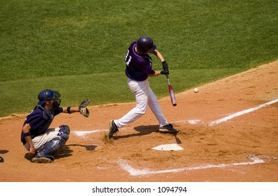 A high school baseball player hits the ball with catcher crouched behind