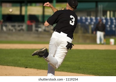 A high school baseball player works on turning the double play from third base.