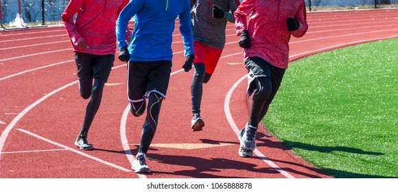 High school boys run a workout together wearing gloves and spandex on a red track during winter track and field practice.