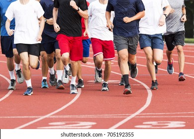 High school boys running in a large group on a red track during cross country practice.