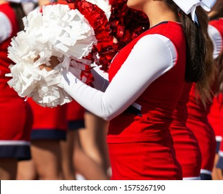A high school cheerleader is facing the stands cheering for her team with red and white pom poms.