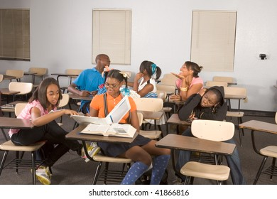 High school classroom with six children, one boy and five girls, making chaos