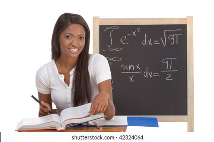 High school or college ethnic African-American female student sitting by the desk at math class. Blackboard with advanced mathematical formals is visible in background