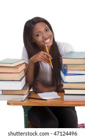 High school or college ethnic African-American female student sitting by the desk with lot of books in class or library and doing homework