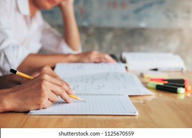 High school or college student group catching up workbook and learning tutoring in classroom and reading, doing homework and lesson practice preparing exam.
