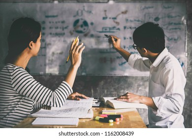 High school or college student group catching up workbook and learning tutoring in classroom and reading, doing homework and lesson practice preparing exam to entrance, education concept.
