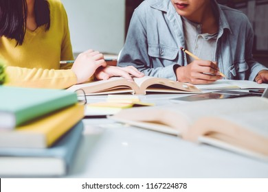 High school or college using laptop while sitting at table. Group students studying and reading with books in library. Students helps friend catching up and learning tutoring. education concepts