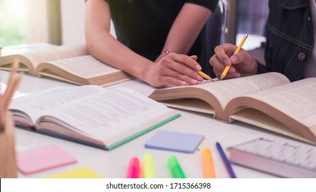 High School oder College mit Laptop während der Sitzung am Tisch. Gruppenschüler lernen und lesen mit Büchern in der Bibliothek. Die Schüler helfen Freunden beim Aufholen und Unterrichten. Bildungskonzepte