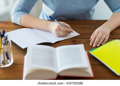 high school, education, people and learning concept - close up of young student or woman with book writing to notebook at home