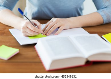 high school, education, people and learning concept - close up of young student or woman with book and notebook writing on sticker at home