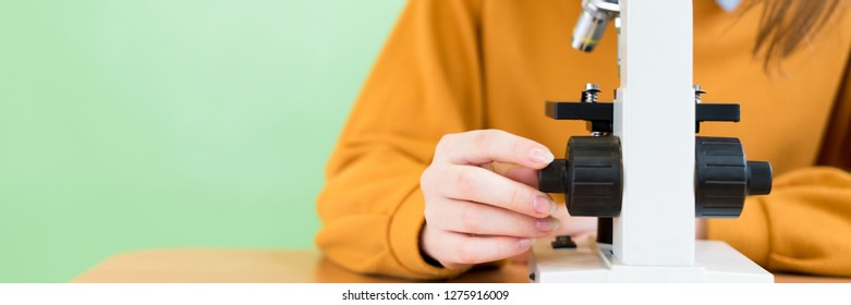 High School female student in biology class. Student using microscope to examine samples.