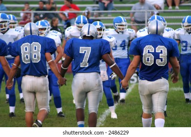 High school football team players entering the playing field with hands linked.