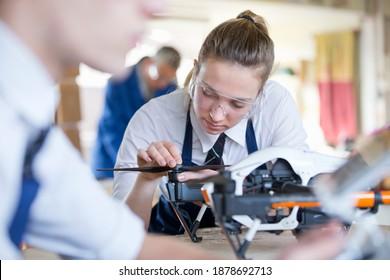High school girl assembling a drone propeller during a shop class.