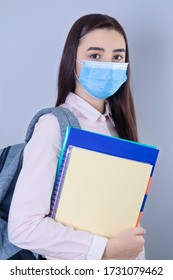 High school girl with mask on her face going back to school. Student girl ready for school during the coronavirus pandemic. Focus on her face.