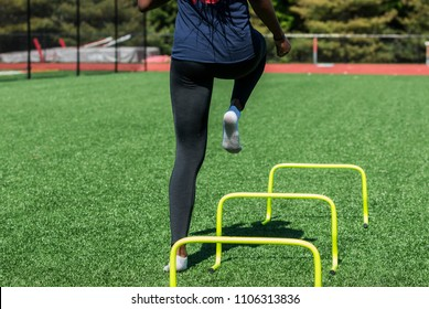 A high school girl is performing speed and agility drills over hurdles with no shoes on, only socks on a green turf field wearing black spandex, viewed from behind.